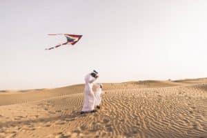 Mann und Kind lassen Drachen in der Wüste steigen