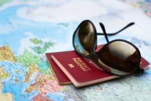 reisepass und sonnenbrille auf weltkarte